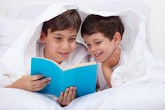 Ungar som läser under filten arkivfoto