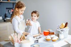 Ungar som lagar mat stekhett kakakökbegrepp arkivfoton