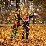 Ungar som leker i höstpark Fotografering för Bildbyråer