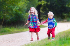 Ungar som leker i höstpark Royaltyfri Bild