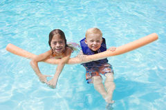Ungar som leker i simbassängen tillsammans Fotografering för Bildbyråer