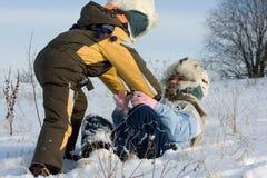 Ungar som leker i snow Arkivbilder