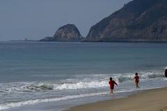 Ungar som leker på stranden Arkivfoto