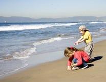ungar som leker sanden Arkivfoto