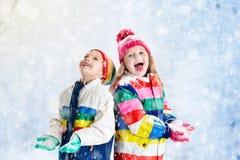 ungar som leker snow Barnlek utomhus i vintersnöfall Arkivfoton