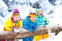 ungar som leker snow Barnlek utomhus i vintersnöfall Royaltyfri Fotografi