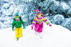 ungar som leker snow Barnlek utomhus i vintersnöfall Royaltyfri Foto