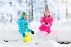 ungar som leker snow Barnlek utomhus i vintersnöfall Arkivbilder