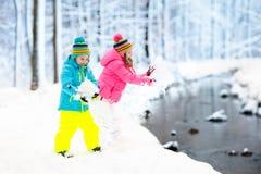 ungar som leker snow Barnlek utomhus i vintersnöfall Arkivbild