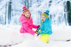 ungar som leker snow Barnlek utomhus i vintersnöfall Arkivfoto