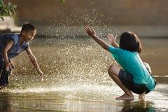 ungar som leker vatten Arkivbild