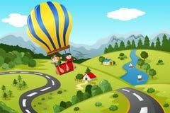 Ungar som rider ballongen för varm luft Arkivfoto
