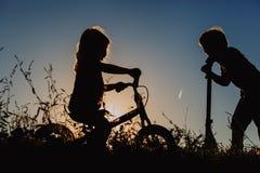Ungar som rider cykeln och sparkcykeln på solnedgången Royaltyfri Bild