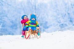 Ungar som rider släden i vinter, parkerar Royaltyfria Bilder