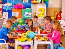 Ungar som in rymmer färgat papper och lim på tabellen fotografering för bildbyråer