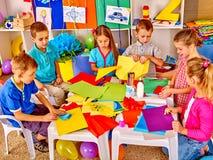 Ungar som rymmer färgat papper på hantverkkurs i dagis royaltyfria bilder