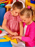 Ungar som in rymmer färgat papper på tabellen Arkivfoto