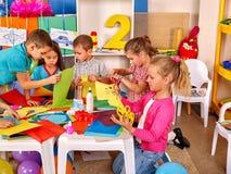 Ungar som rymmer färgat papper på tabellen i dagis Royaltyfri Foto