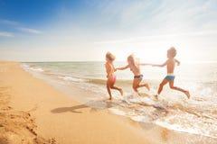 Ungar som rymmer händer och spring längs den sandiga stranden royaltyfri fotografi