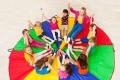 Ungar som rymmer händer samman med lärare i idrottshall Royaltyfria Bilder