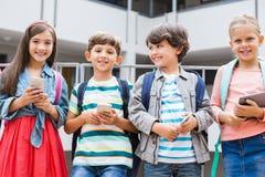 Ungar som rymmer mobiltelefonen och digitalt minnestavlaanseende på skola, terrasserar arkivbilder