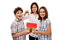 Ungar som rymmer modellen av huset isolerad på vit Arkivbild