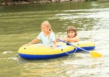 Ungar som seglar i stakbåt Arkivbild