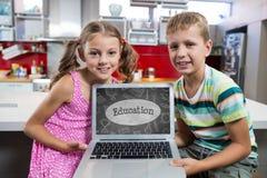 Ungar som ser en dator med skolasymboler på skärmen Royaltyfri Fotografi