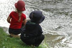 ungar som ser floden Arkivfoto