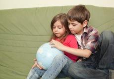 Ungar som ser jordklotet Royaltyfria Bilder