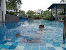 Ungar som simmar på simbassängen royaltyfria foton
