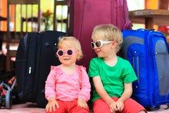 Ungar som sitter på resväskor som är klara att resa arkivfoton