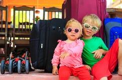 Ungar som sitter på resväskor som är klara att resa arkivbilder