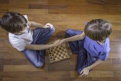 Ungar som skakar händer för lek av schacksammanträde på trägolv Top beskådar arkivfoton