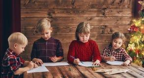 Ungar som skrivar brev till Santa Claus Royaltyfria Bilder