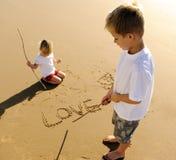 Ungar som skriver i sand Arkivbild