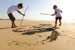 Ungar som skriver i sand arkivbilder