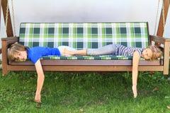 Ungar som sover på en trädgårds- gunga Arkivbild