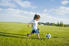 Ungar som sparkar fotboll, klumpa ihop sig Royaltyfri Fotografi