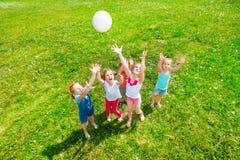 Ungar som spelar bollen på en äng Arkivfoto