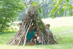 Ungar som spelar bredvid träpinnen, inhyser att se som indierkoja, Arkivfoto
