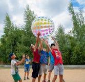 Ungar som spelar den stora uppblåsbara bollen Lek för lagbyggnad royaltyfri bild