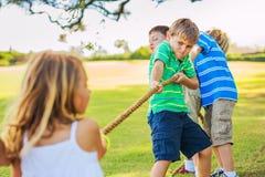 Ungar som spelar dragkampen Arkivfoton
