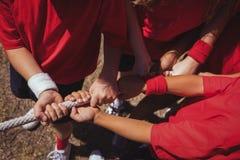 Ungar som spelar dragkampen under utbildning för hinderkurs royaltyfria bilder