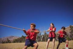 Ungar som spelar dragkampen under utbildning för hinderkurs fotografering för bildbyråer