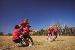 Ungar som spelar dragkampen under utbildning för hinderkurs royaltyfria foton