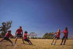Ungar som spelar dragkampen under utbildning för hinderkurs arkivfoto