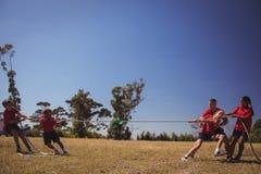 Ungar som spelar dragkampen under utbildning för hinderkurs royaltyfri bild