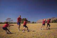 Ungar som spelar dragkampen under utbildning för hinderkurs royaltyfri foto