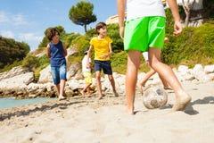 Ungar som spelar fotboll barfota på den sandiga stranden Royaltyfria Bilder